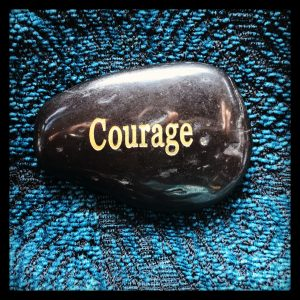 "Close up of a shiny, black rock with the word ""Courage"" written upon it in gold letters. Rock is on blue fabric."